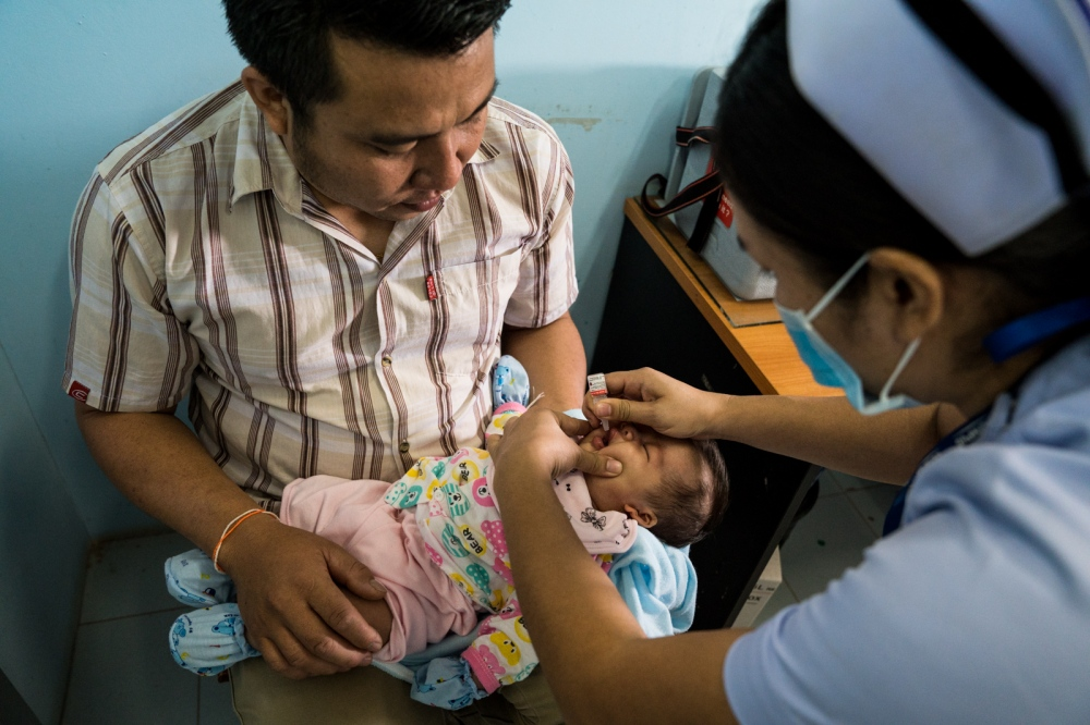 Baby receiving a polio vaccine. Laos.