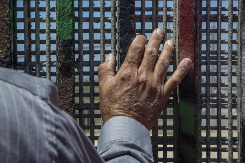 Pastor Guillermo Navarrete of the Methodist Church of Mexico at the border fence during the weekly meeting of the Border Church in Tijuana, Mexico. The binational service is conducted simultaneously on both sides of the border fence in English and Spanish.