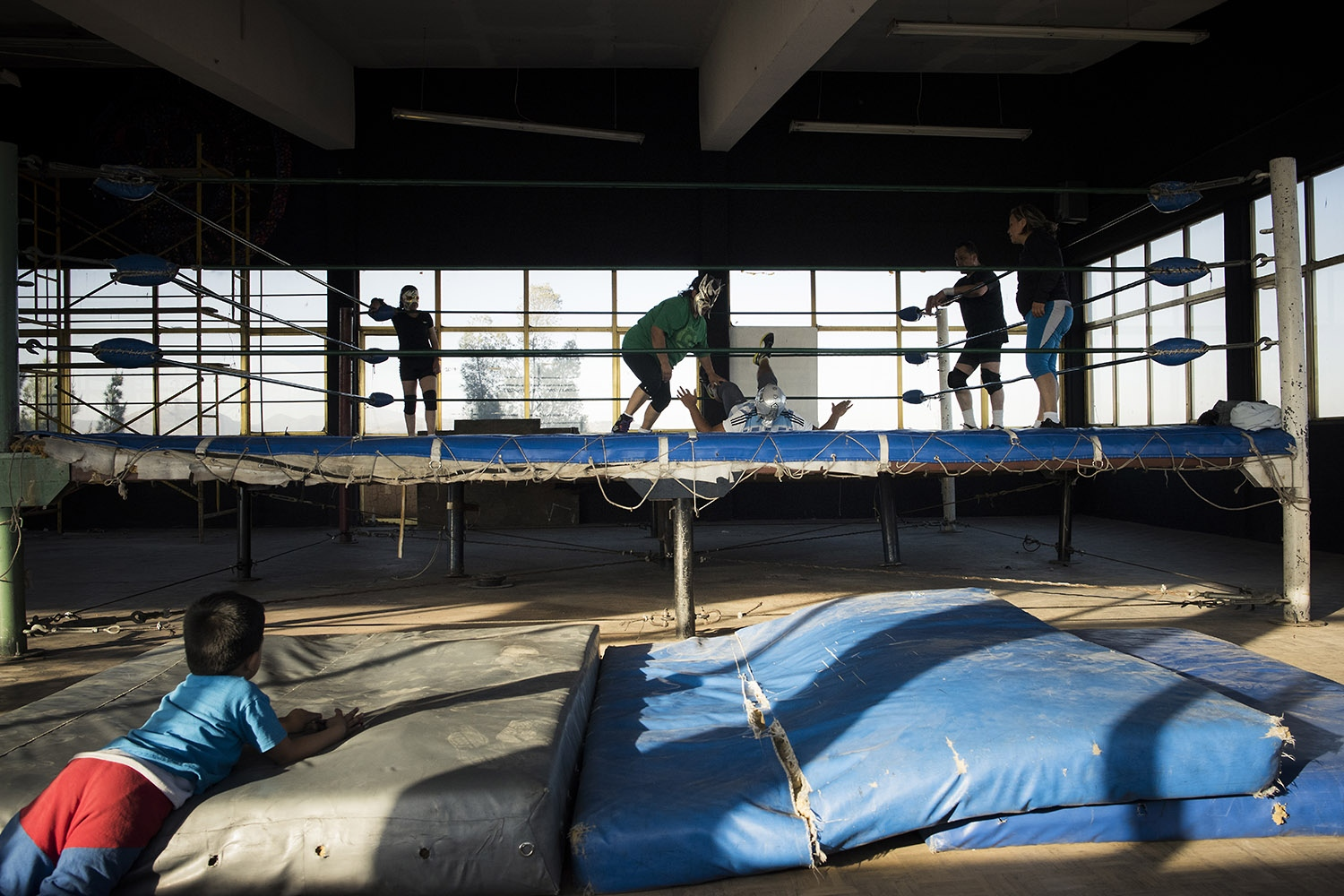 A child is watching his mother's training in a Mexico City's wrestling gym.