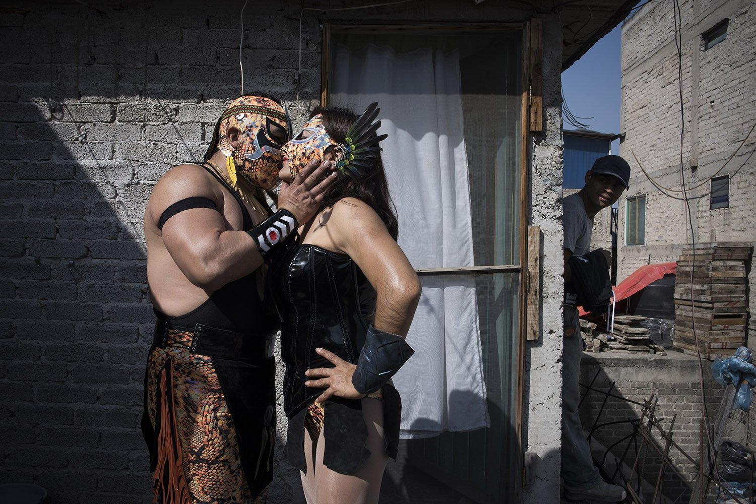 Xenia kissing her new husband in the backyard of their house in Mexico City, while her third son is watching them. Her first husband was abusive and didn't allow her to fight. It took her 14 years to get out from that marriage and get back in the ring. Here she met her new husband, 20 years her junior