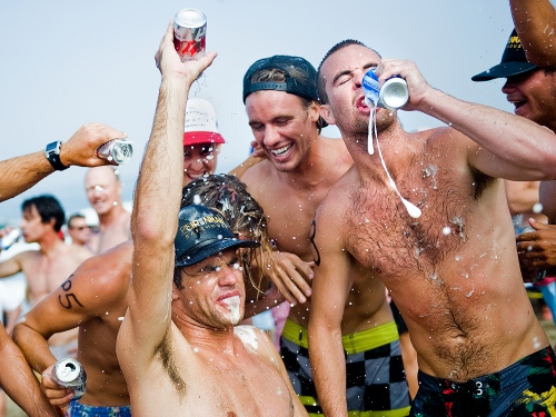 Participants of the Hermosa Beach Iron Man on the 4th of July chug six-packs of beer as fast as they can after running down the beach and swimming back.