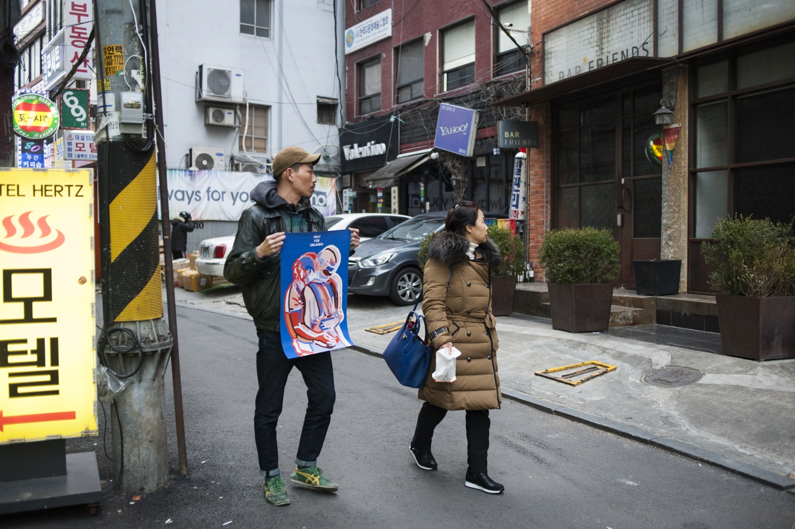 Artist and illustrator Nahwan Jeon (b. 1984)stands in front of his favorite LGBT friendly spot in Seoul, Bar Friends, which was the first gay bar to open in Jongro. Jeon is holding a poster he designed to commemorate the Pulse nightclub shooting in Orlando, Florida.
