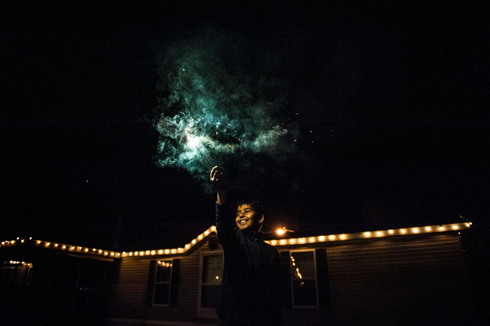 "Anirudh Sharma waves a sparkler above his head during a Diwali celebration Saturday night at the Shanthi Mandir in Columbia. The five-day holiday, also known as the ""Festival of Lights,"" is one of the most important in the Hindu faith."