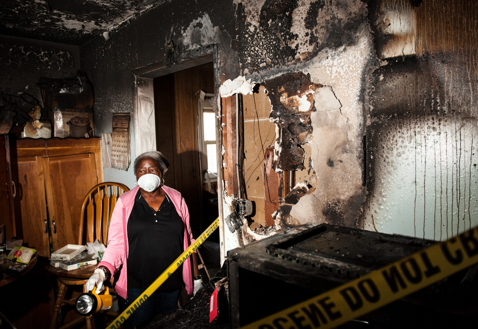Dottie Mulkey, 74, walks through her damaged kitchen in Santa Ana after a December fire. Mulkey's homeowner's insurance had lapsed at the time of the blaze leaving her unable to restore her home.