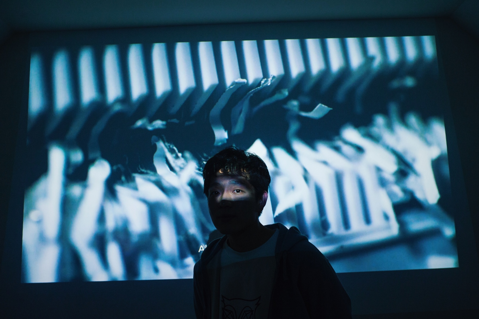 """Writer and artist Jungsik Lee (b. 1987) poses in front of his video piece, """"That Book (2017),"""" at LASER gallery, Yeonnam-dong, Seoul. Lee was diagnosed with HIV in December 2013 and has since made work that reflects his experience, interpretation of how HIV-positive individuals are perceived in Korea, and other """"diseases of modern society"""" such as isolation and despair. In this piece, Lee appears in front of the camera in a colorless room. His voice recites a book while his sitting figure scribbles on a blank notebook, then rips and shreds it apart. Through actualizing his experience and beliefs as pieces of artwork, Lee seeks to communicate his existence with the public and fight the urge to hide from Korean society. Lee felt different and alienated in his hometown of Daejeon from a young age, left, and spent time at youth centers during his teenage years. Those with HIV/AIDS are ostracized even within Korea's LGBTQ community, a marginalized group in its own right. """"The general attitude toward HIV/AIDS patients has not changed since the 90s. With one's diagnosis comes isolation,"""" said Lee, explaining that such an attitude makes it difficult for individuals to accept and seek treatment."""
