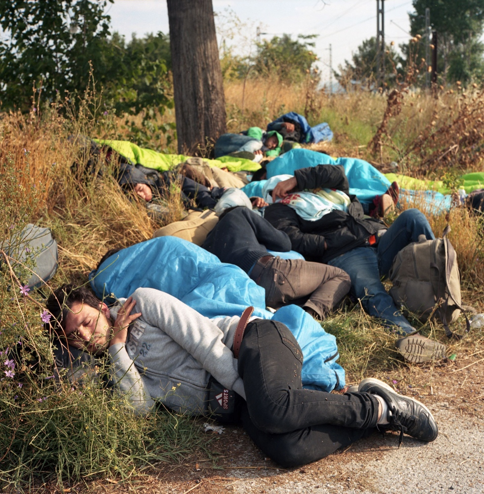 Syrian refugees huddled in the fields of Idomeni, a small Greek town on the border with Macedonia. The border was closed and patrolled by the Macedonian police. Migrants waited till nightfall to cross through the forests and fields into Macedonia.