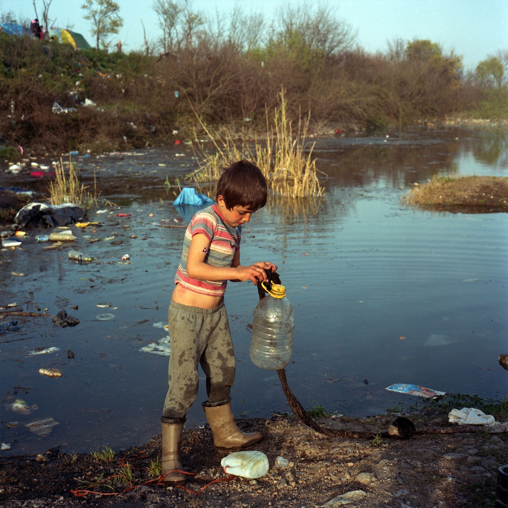 Syrian refugee boy plays with a plastic bottle by the pond in Idomeni.