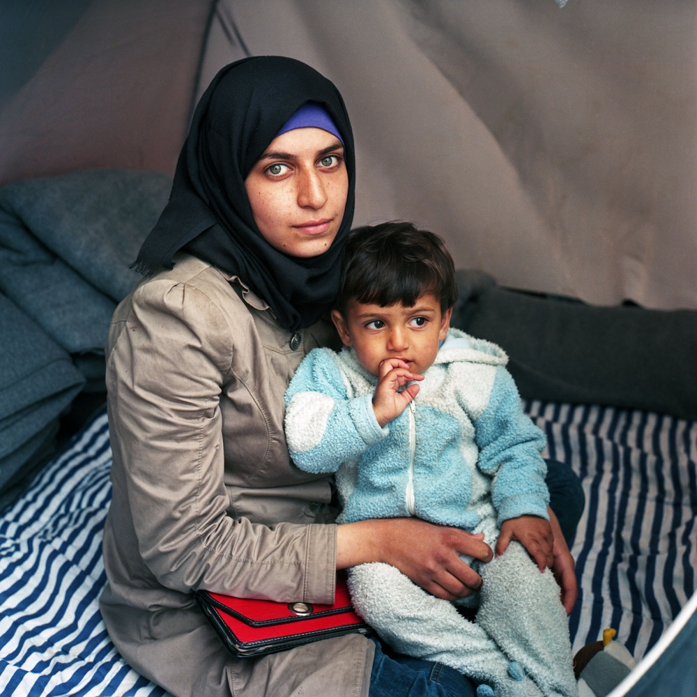 Syrian refugee mother and her son in a tent in Idomeni.