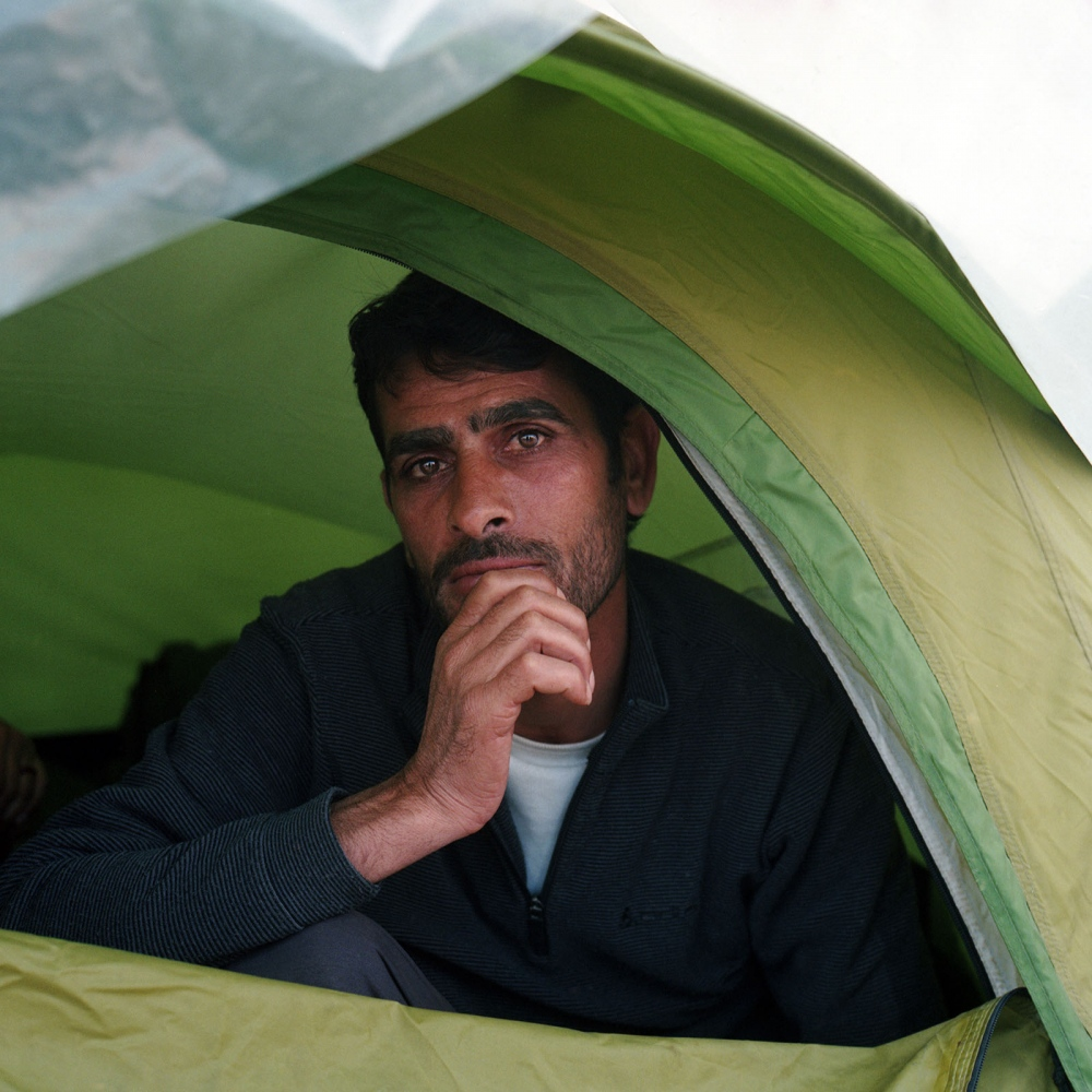 Syrian refugee man inside his tent in Idomeni, Greece. Thousands waited by the sealed border with Macedonia for a chance to cross into Europe, but the makeshift camp was eventually shut down, Greek riot police moved in on the camp and cleared it of all remaining residents. People were ordered to move to the government-run camps throughout Greece, where many of them still remain waiting for their paperwork to get processed.