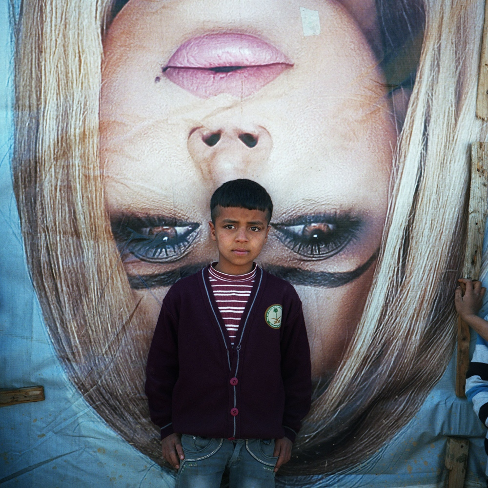 Syrian refugee boy outside a tent made out of billboard canvasses with an image of Lebanese pop star Nawal El Zoghby in an informal settlement of Syrian refugees in the Beqaa Valley in 2014.