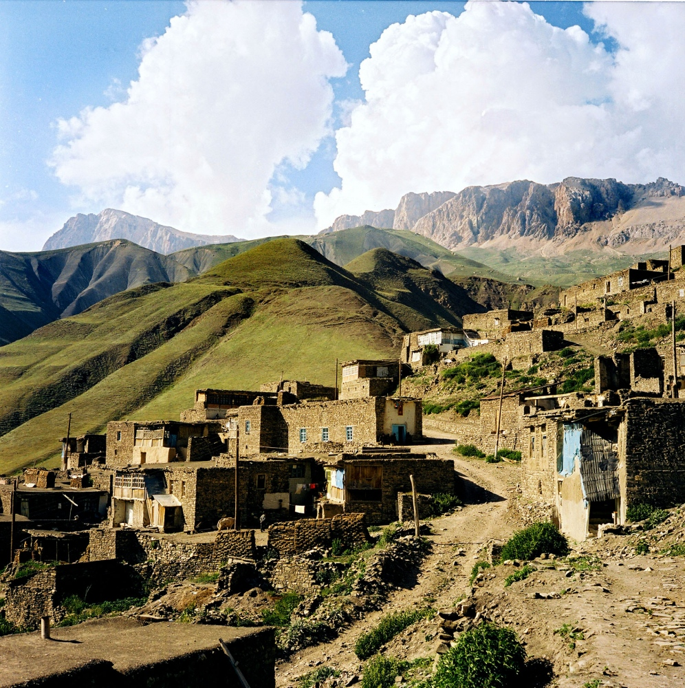 View of the village, homes built into the mountain with traditional, locally harvested materials, wood and river stones. A roof of one home serves as a courtyard for the next building. Khinaliq, Azerbaijan. 2006