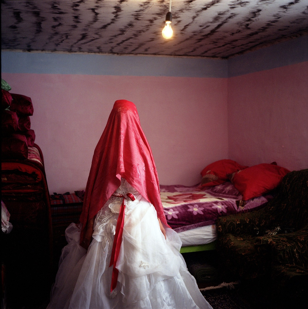 The bride covered in red silk waits at home for her final appearance in the wedding party. Khinaliq, Azerbaijan. 2009
