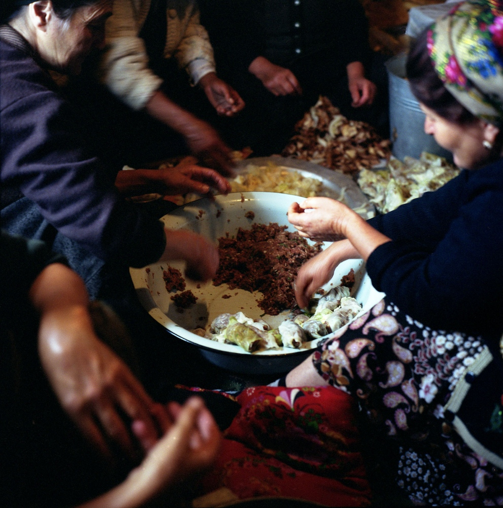 Women making Kelem Dolmasi for the wedding guests, a dish of minced mutton wrapped in cabbage leaves. The village diet mostly consists of mutton based meals. Khinaliq, Azerbaijan. 2009