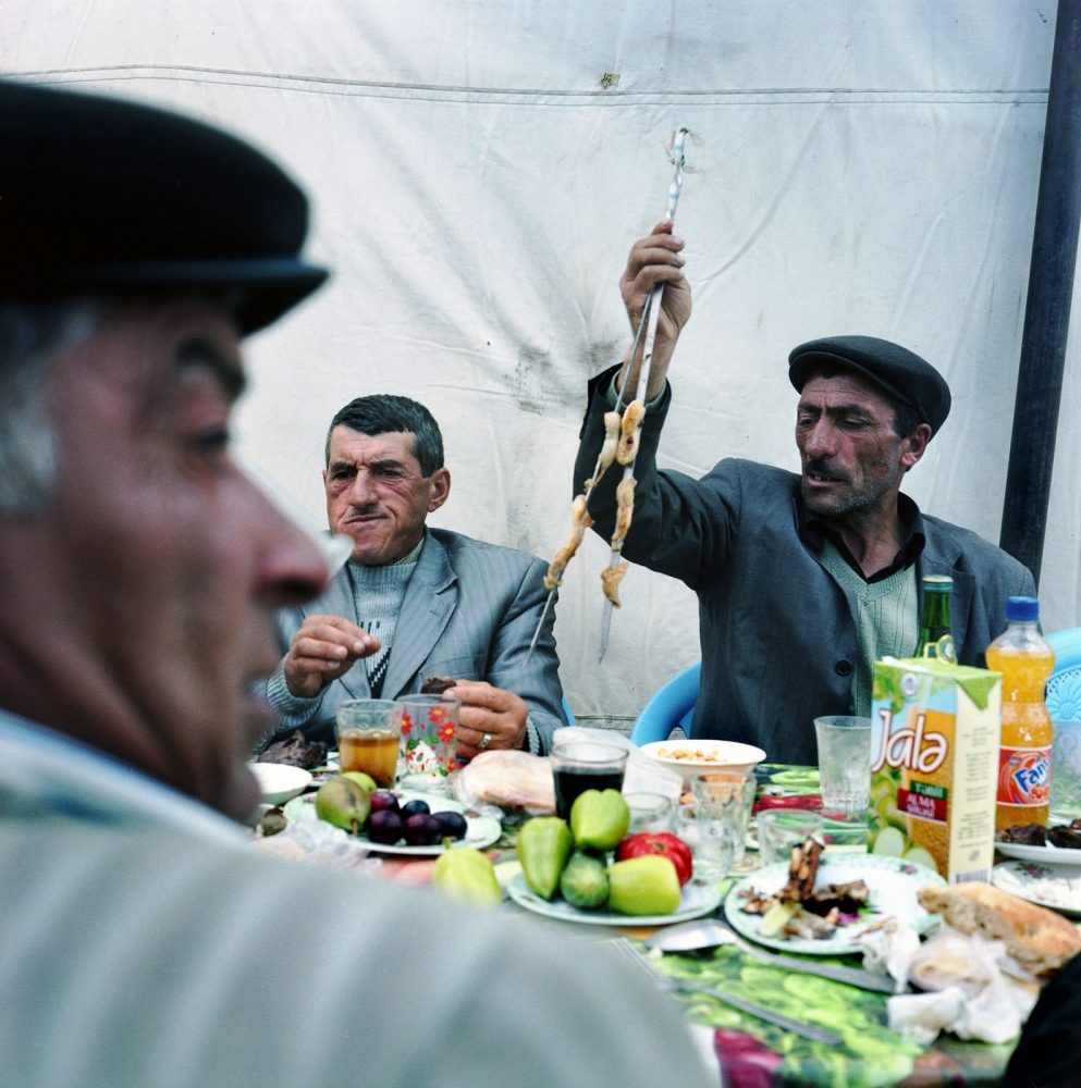 Men eating lamb kebabs inside the wedding tent. Women and men are separated during the wedding meal. Khinaliq, Azerbaijan. 2009
