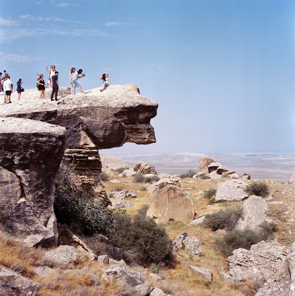 Visitors pose in the Gobustan Preserve, site of rock art dating back 40,000 years–and one of the highest concentrations of gas-fueled mud volcanoes on Earth.