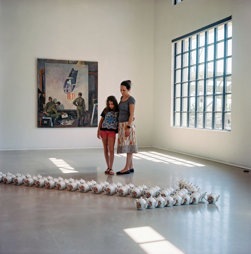 Visitors at the Yarat Contemporary Art center ponder overZamir Suleymanov's installation of teapots forming an arrow.