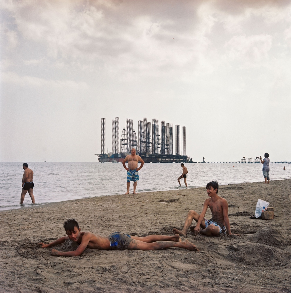 Families enjoy downtime with idle Soviet oil rigs at Shikhov beach, 10 miles south of Baku.
