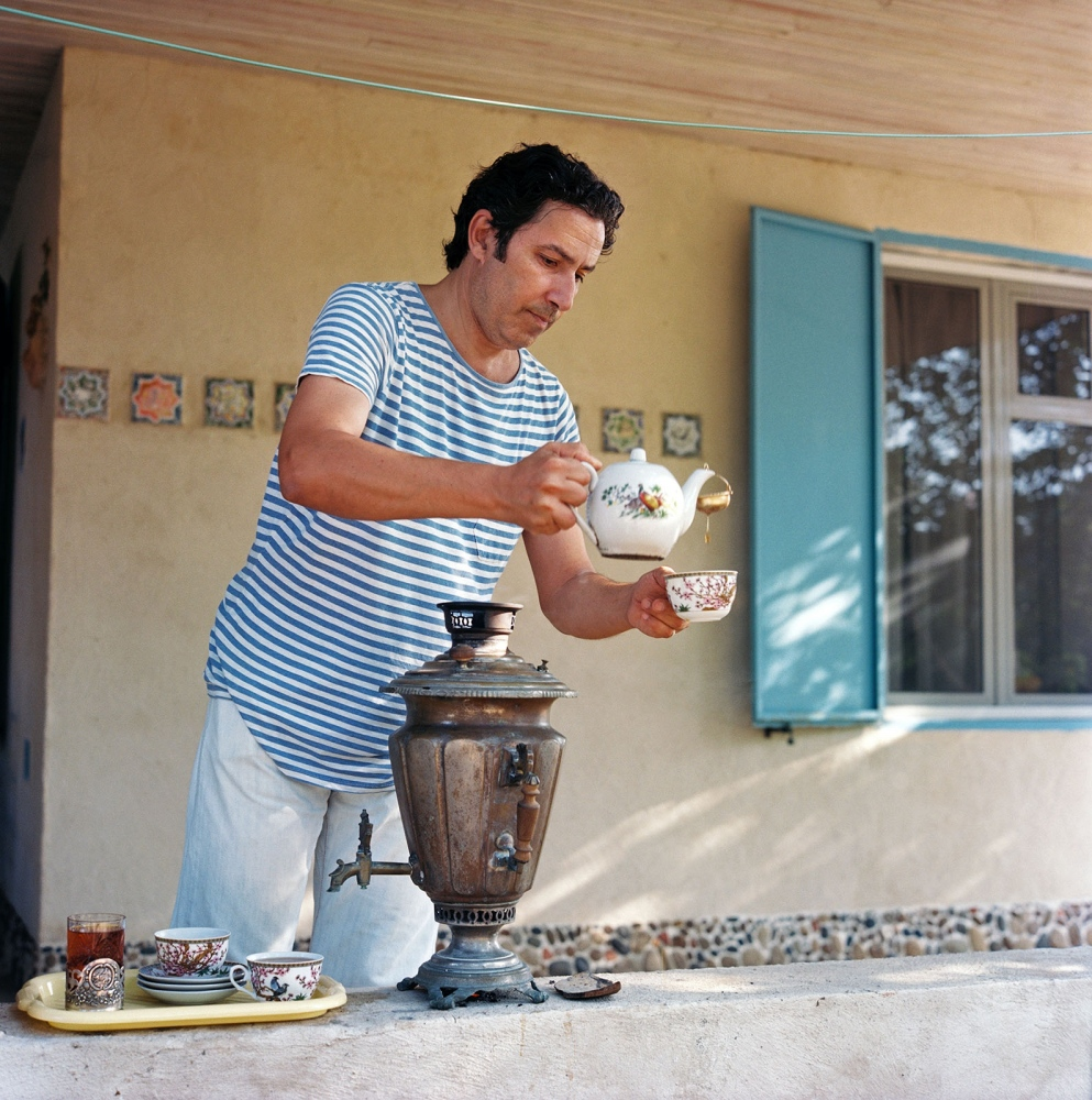 Artist Elnur Babayev pours a cup of tea at his family dacha in Nardaran village on the Caspian Sea.