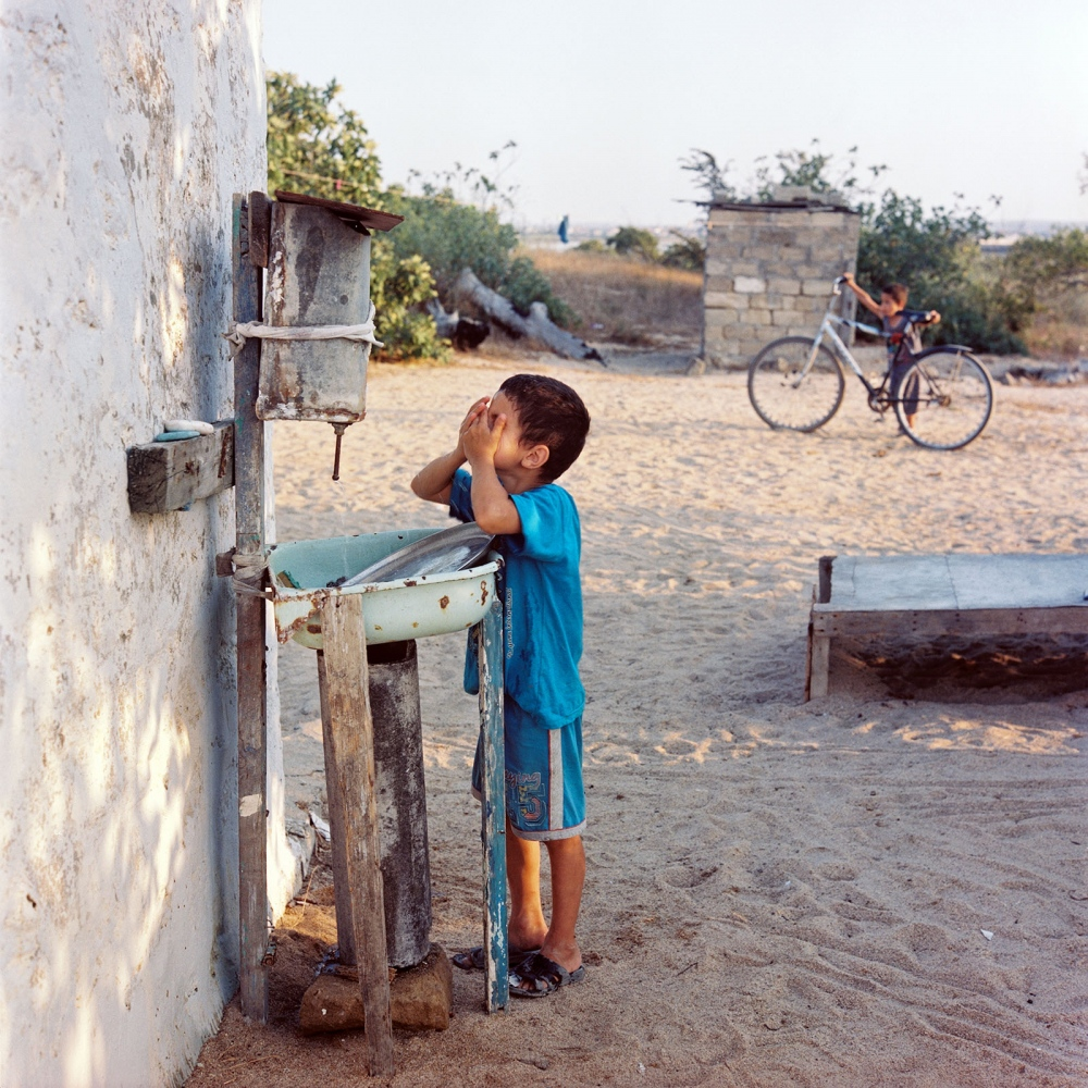 Boy washes his face with water from a traditional drip fountain in Kurdakhani village on the outskirts of Baku where many people have their 'dachas', or summer residences.