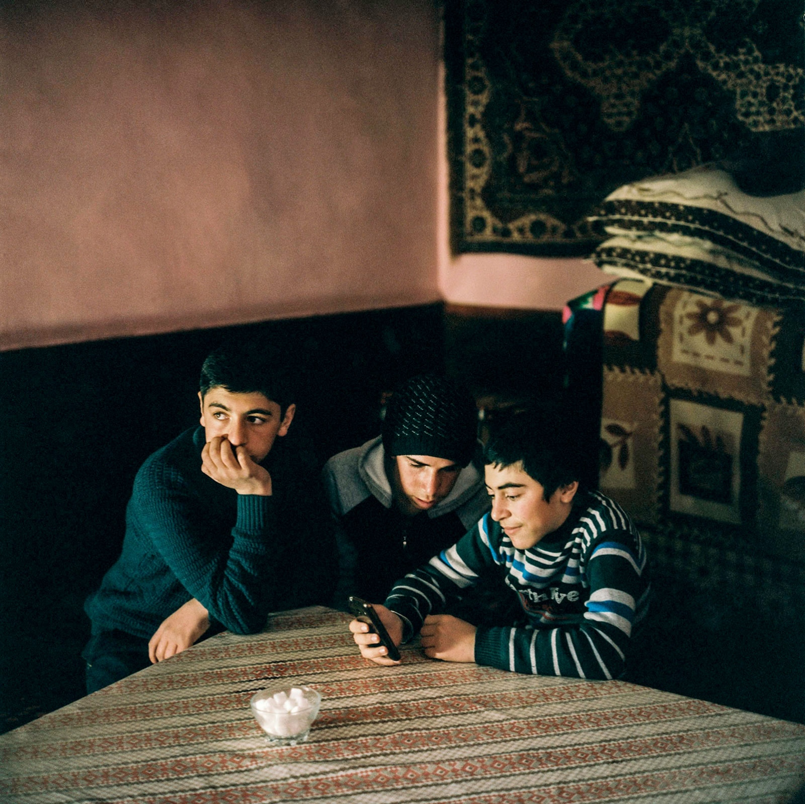 Brothers Samir and Izzet at home. More youth is using smart phones in Khanaliq, the village has not had a phone connection up until 2007. Khinaliq, Azerbaijan. 2018