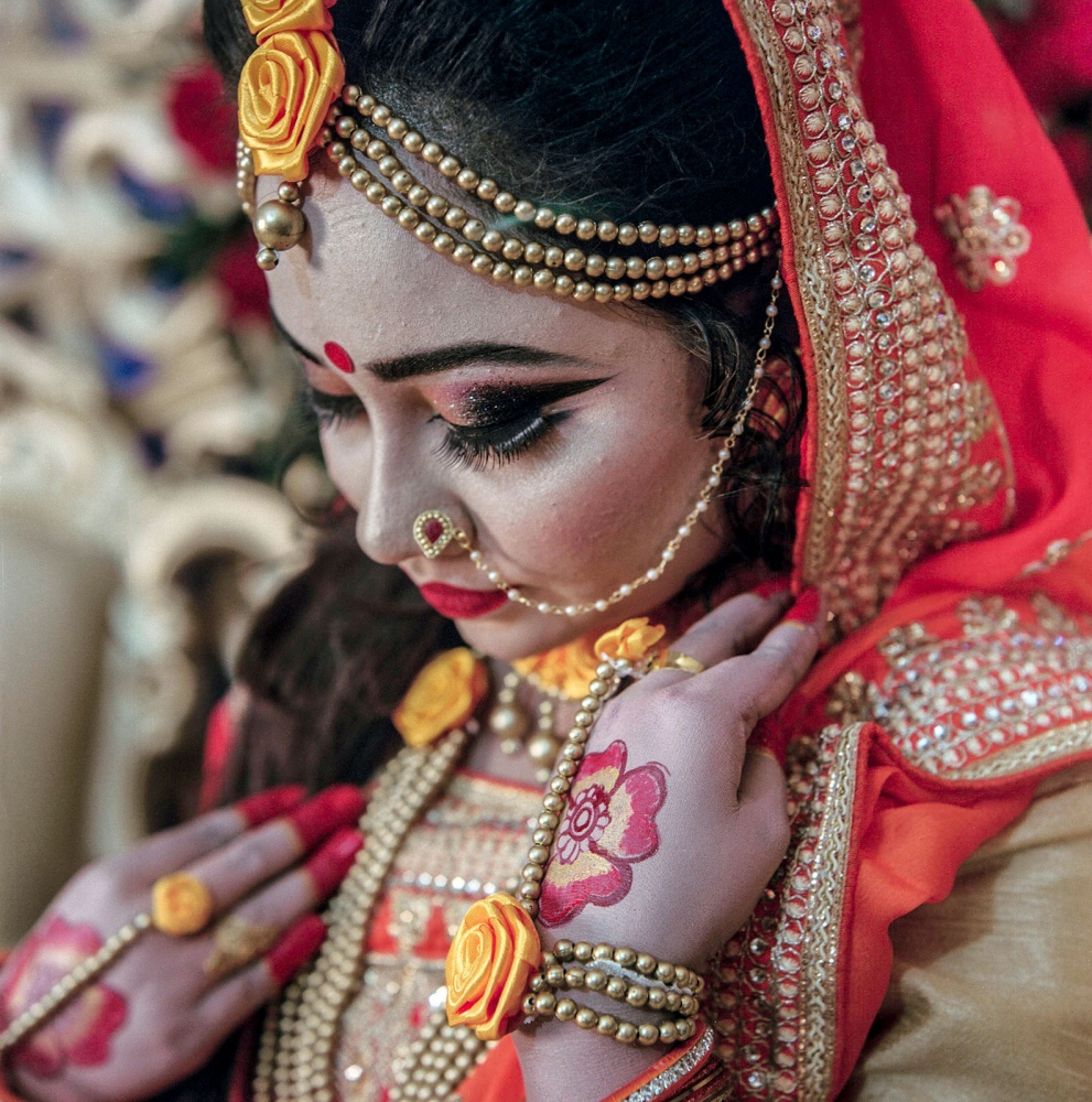 Bride Moly Sufia at her gaye holud in Kerenigonj a ceremony where guests cover the couple in turmeric paste and feed them sweets.