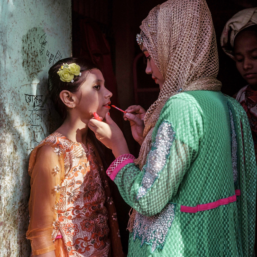 Cousin of the bride applies lip gloss to her younger sister's lips to prepare for the wedding party in Manehor.