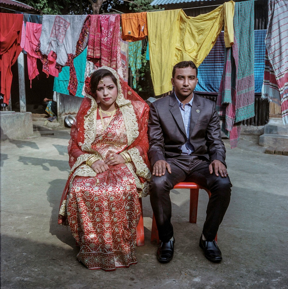 Nargis and Rajib celebrate their wedding reception in the courtyard of the groom's home. This is their first official appearance as a married couple. A tent is erected in their village near Gazipour to greet guests and serve food.