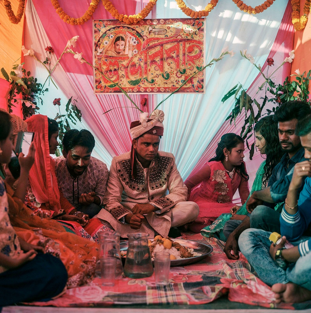 The groom, Bilal, nervously waits for his bride as he shares a plate of palau and roast chicken with his family and his soon-to-be sisters-in-law Manehor, Bangladesh.