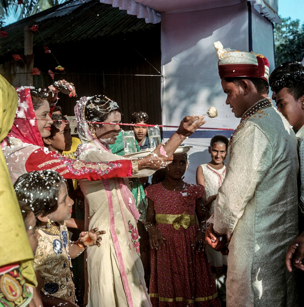 Bride's party blocks the groom's entrance into the wedding with a red ribbon demanding that he pays a bribe. A playful tug of war ensues while the groom attempts to find a cunning way to avoid payment and break through the cordon.