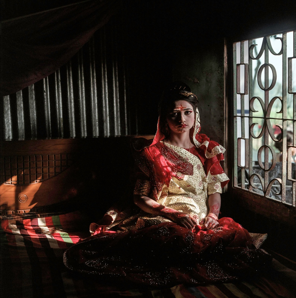 Ratna, wearing her full wedding day garb, waits by the window of her childhood bedroom where she can watch as guests arrive.
