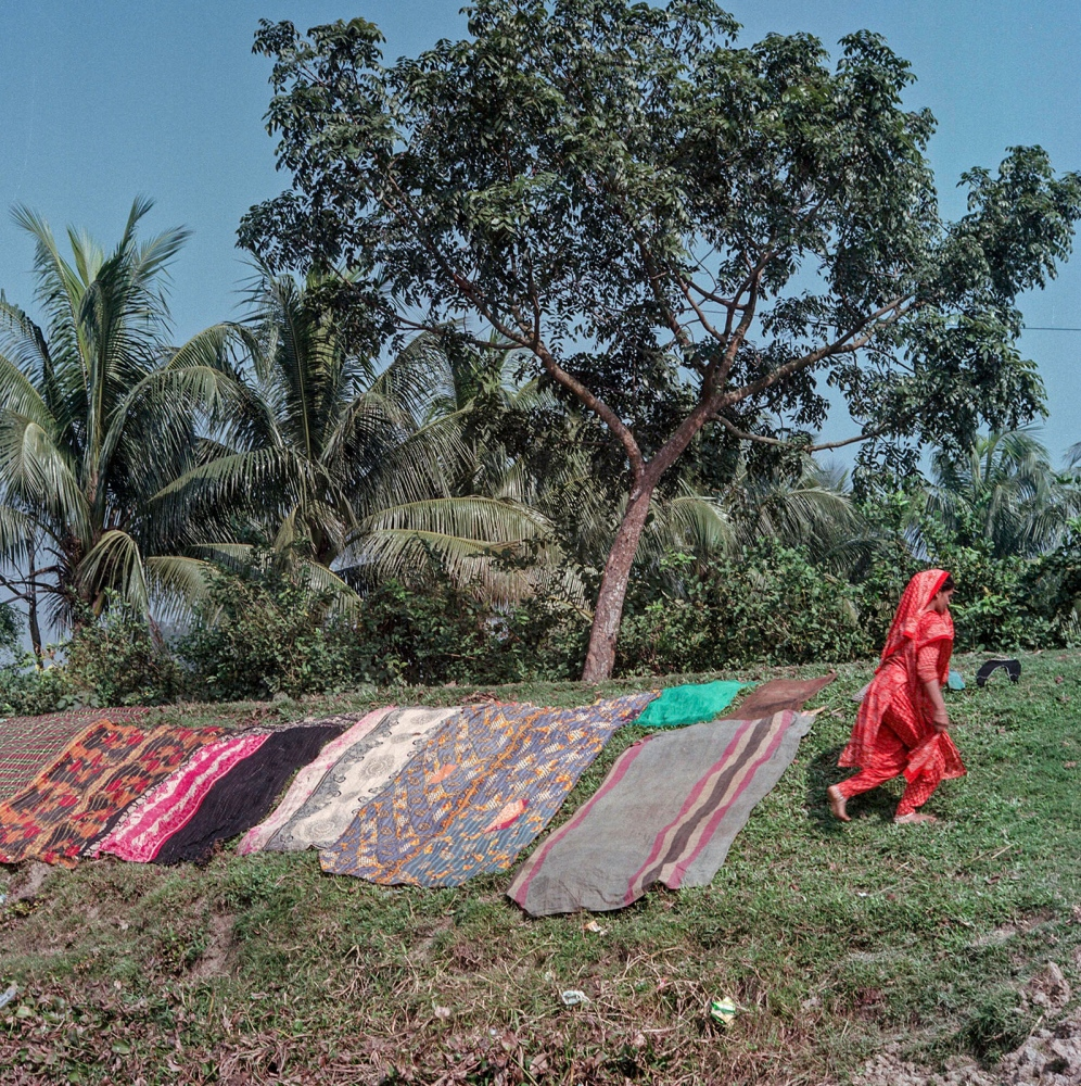 Saris are laid out to dry as the village prepares for a wedding festivity later that afternoon in Manehor.