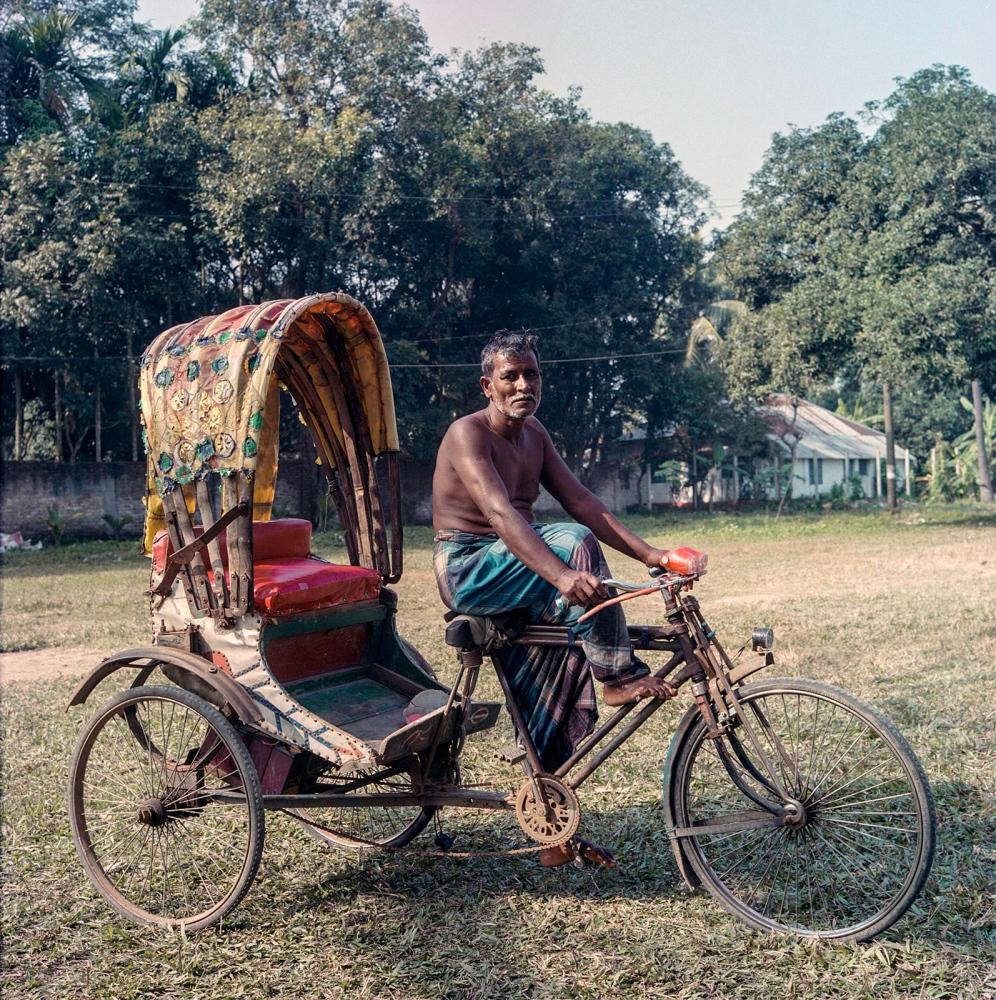 A rikshawalla waiting for his turn to take a bath inside a village pond in Manehor.