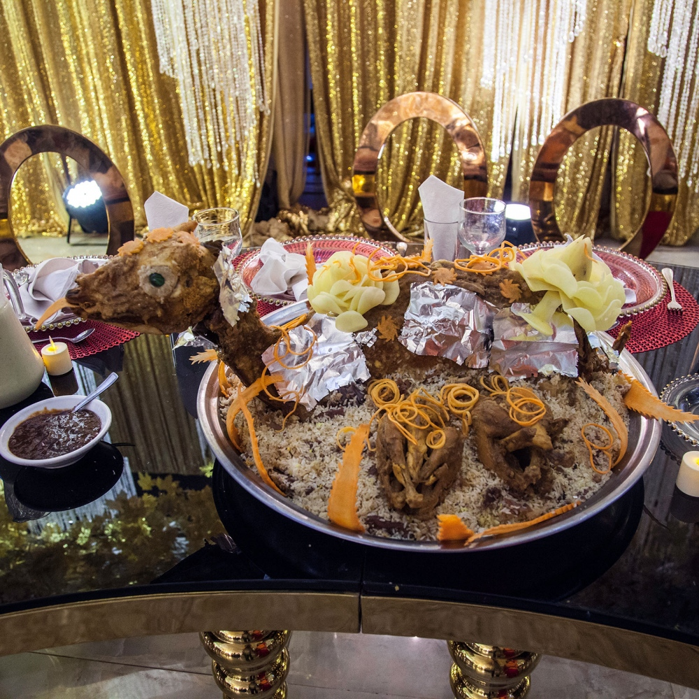 A table set up for the bride and groom's party. The groom is served an entire goat buryani on heaps of saffron rice.