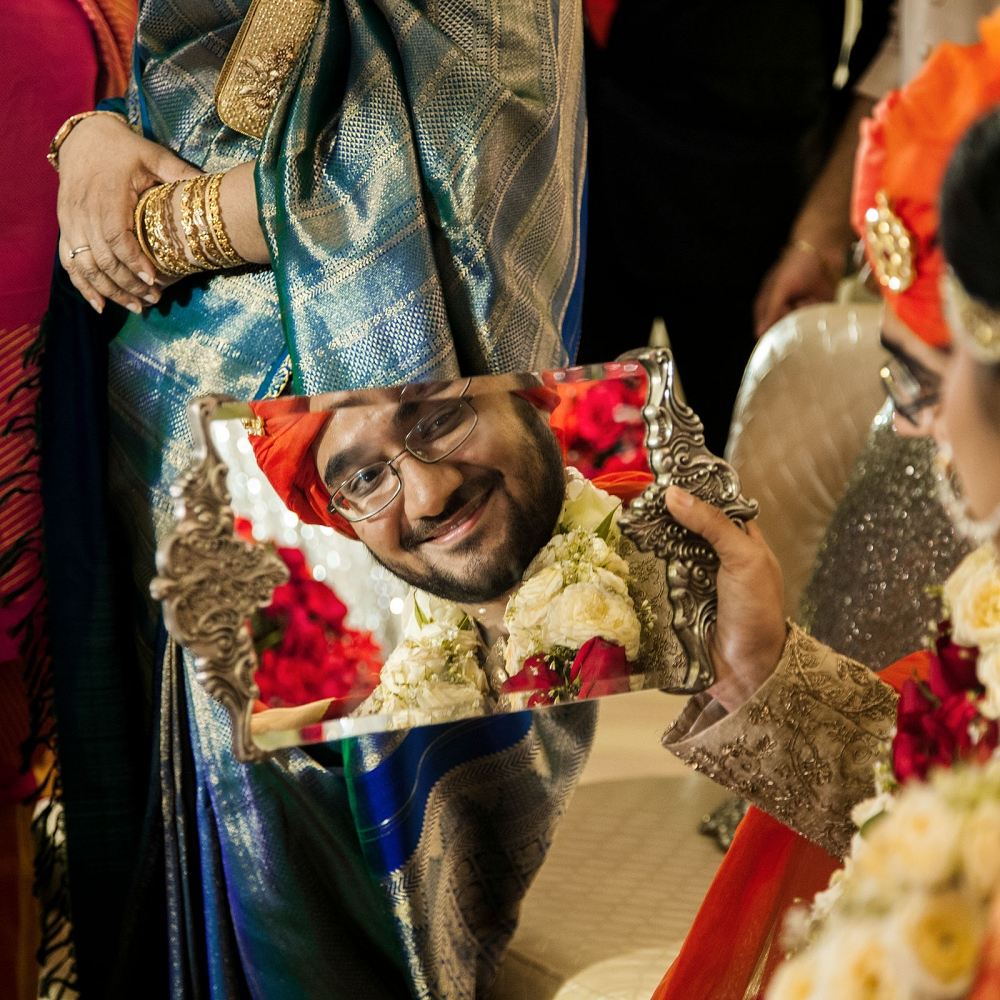 A groom smiles back at his bride in the reflection of the mirror during a wedding ritual of rusmat in Dhaka.