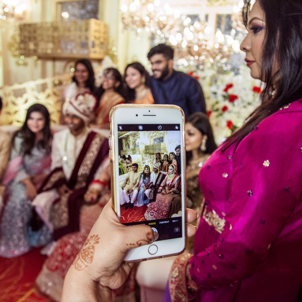 More than 2000 wedding guests in a lush wedding in Dhaka line up to be photographed with the bride and groom. Immediate family members are given the first priority.
