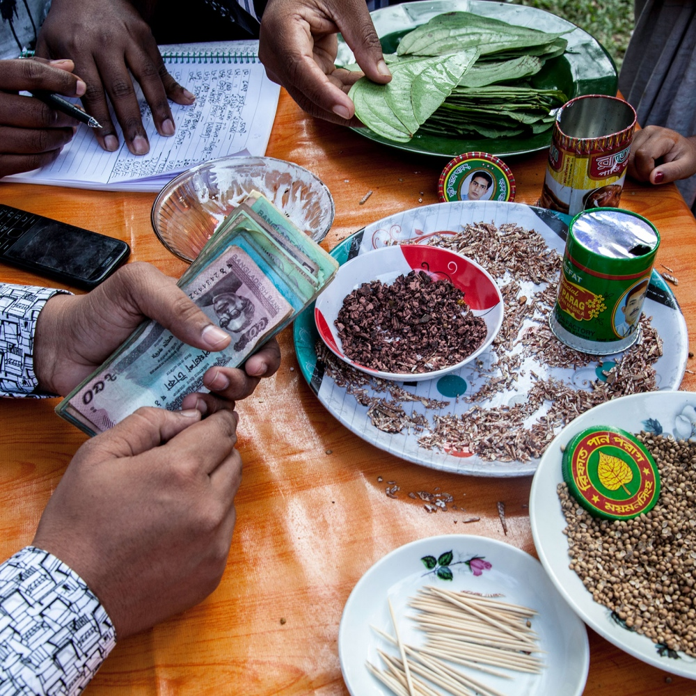 A table is set up for a wedding registry in Gazipour where family members count the money presented by the invited guests.