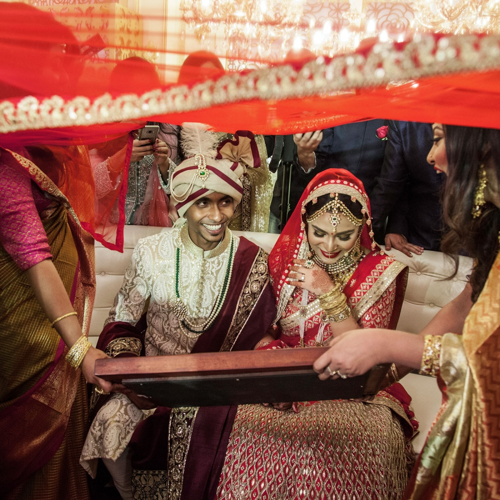 At a city wedding in Dhaka, the newlywed couple participates in the  rusmat , a Bengali tradition during which the bride and groom exchange rings and flower garlands, as well as gaze at each other through a mirror.