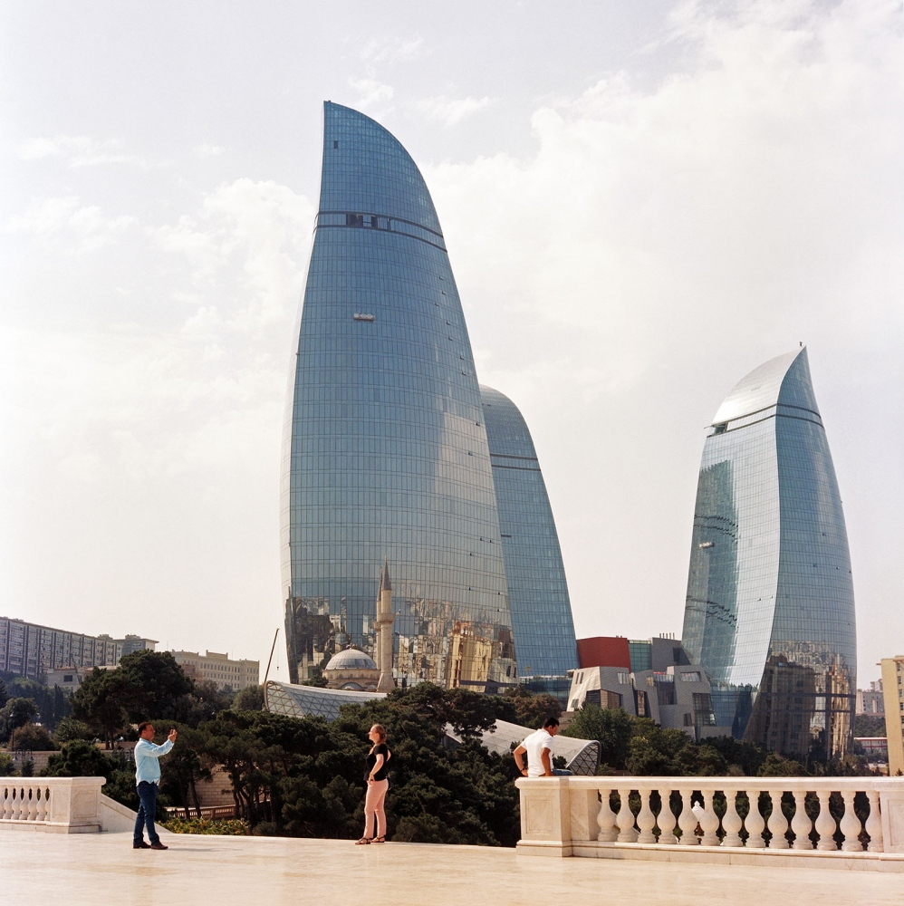 Sahidler Xiyabani mosque reflects in one of the three Flame Towers, as seen from the terrace of the Dagustu park in Baku.