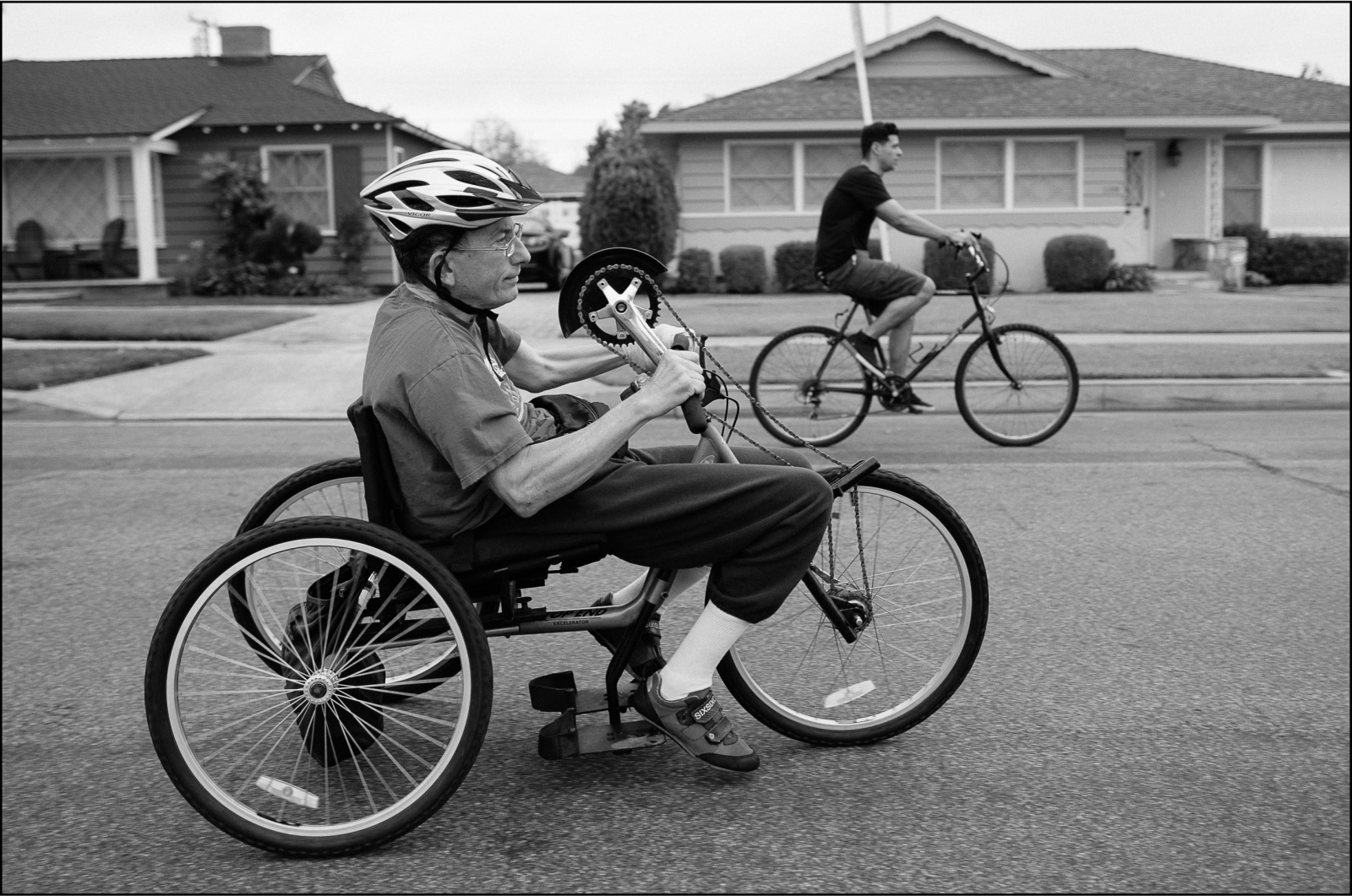 Arthur Blaser rides his tricycle with Isaac R. Larios around his neighborhood on Wednesday, July 22, 2015. Larios assists Blaser every weekday; they meet every morning at 6:40AM to exercise.