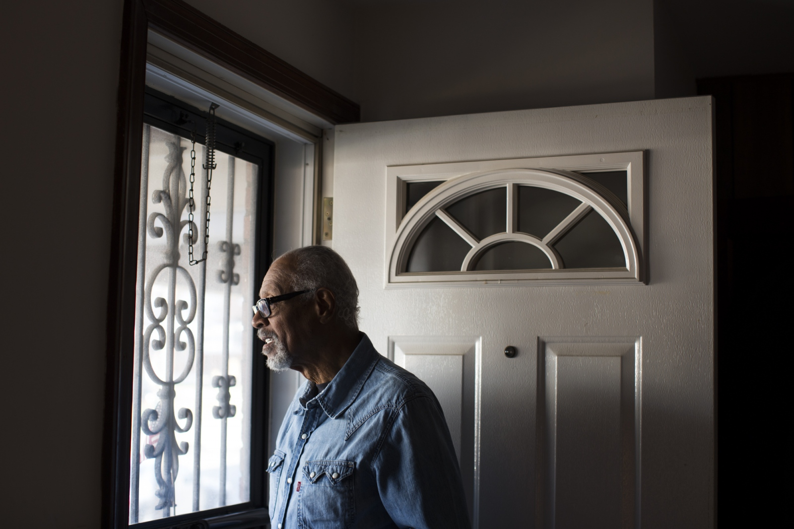 """Mr. Lenny"" - Washington, D.C., December 2015.  Lawrence E. Leonard Sr., 81, looks outside his front porch Friday, Dec. 4, 2015. Leonard has been a resident of Fairlawn in Ward 8 in Washington, D.C. for 41 years. Leonard watched over many of the children on the block during his early years as a resident and was affectionately named ""Mr. Lenny."""