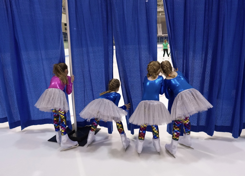 Photography image - Young figure skaters sneak a peek at more experinced performers at the Middlebury College Winter Carnival Ice Show, Middlebury, Vermont.