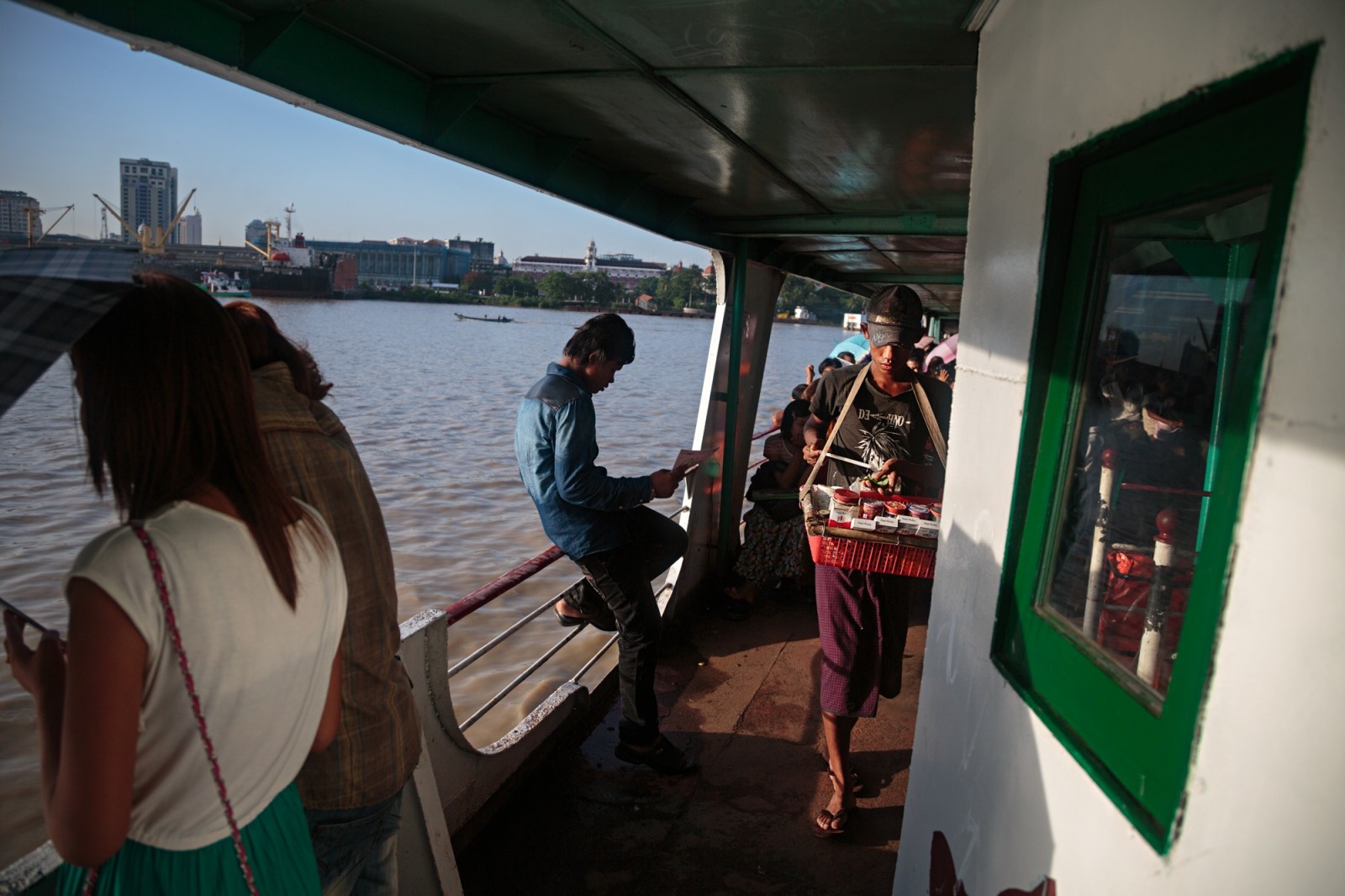 Passengers cross the Yangon river to Dala. A bridge is in the works to connect Yangon and Dala which will transfrom the quiet rural area into a bustling waterfront. Poor residents along the waters edge in Dala are already being forced to sell their homes.