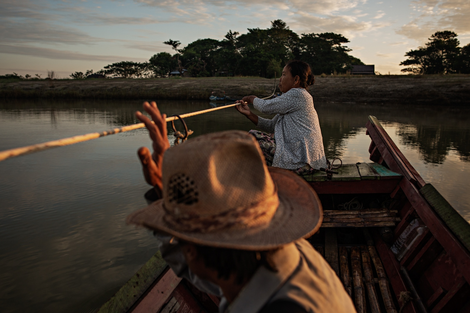 A man rides a boat across the river in Hinthada, powered by the woman pulling on the rope.