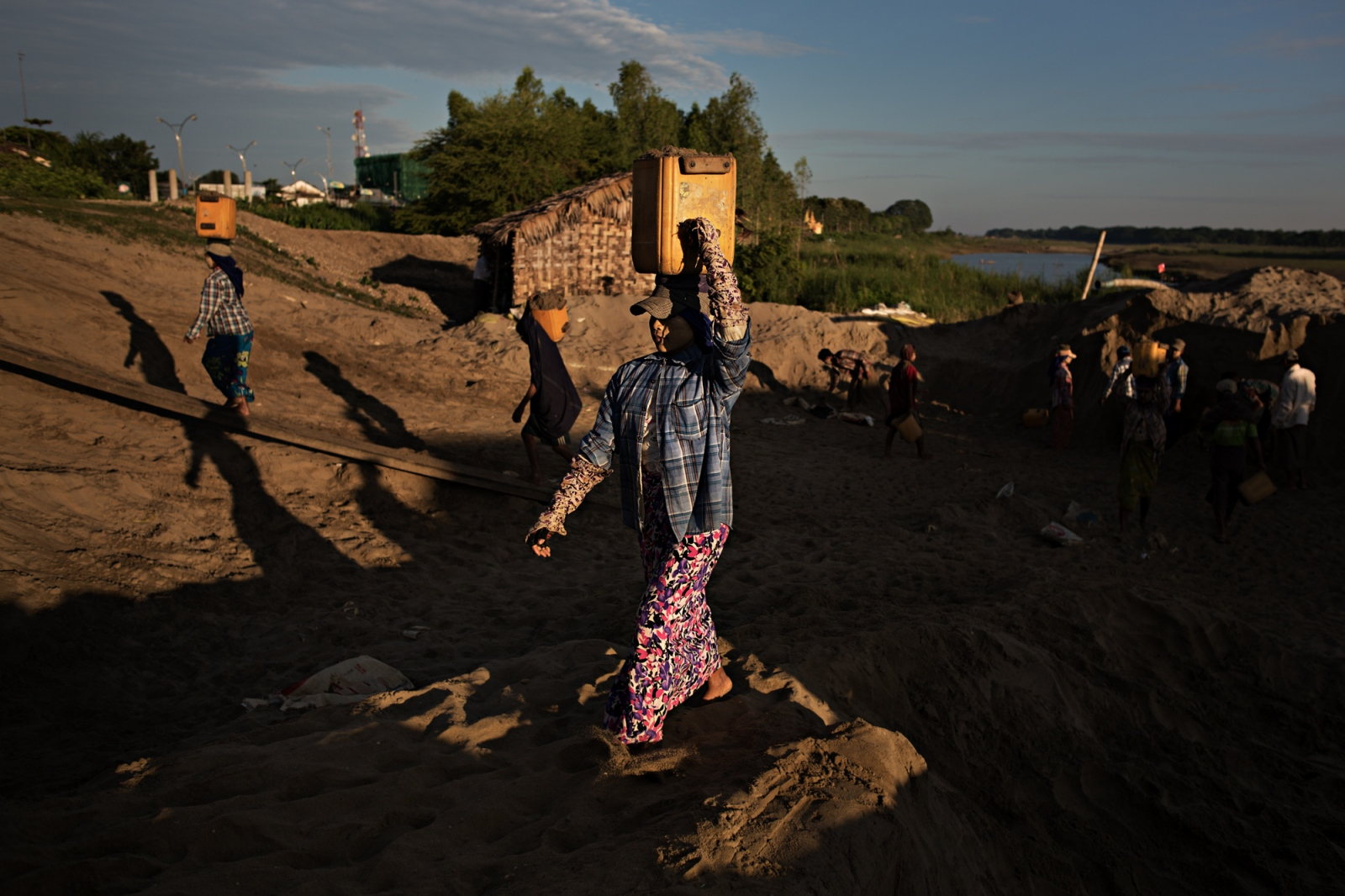 A woman carries sand to a waiting truck. Sand mining is very profitable becasue of how many uses there are for it, but it also causes a lot of environmental damage. It is not well regulated.