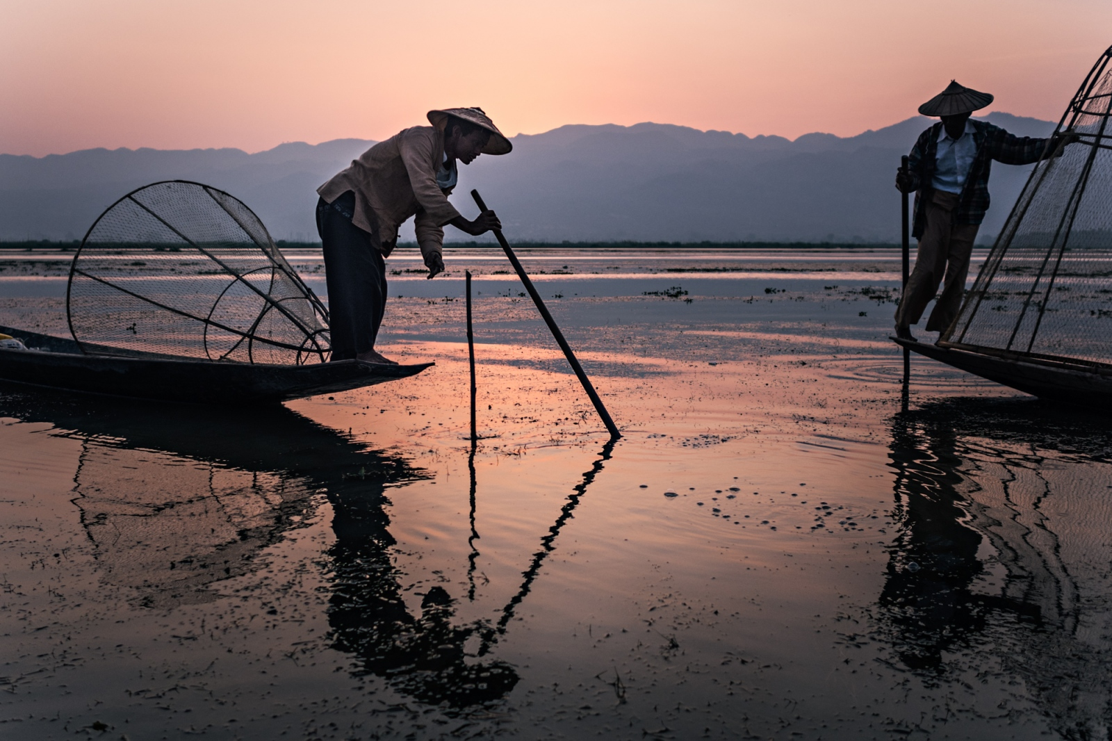 Intha fishermen demonstrate traditional fishing methods at dawn on Inle Lake. Due to shrinking lake size, over fishing, pollution and the price of living, traditional methods of fishing are no longer viable in earning a living and are only practiced for show.