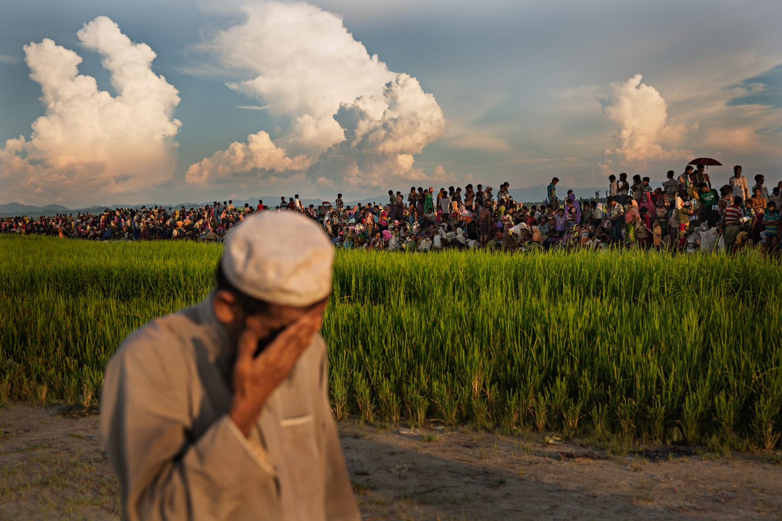 Abu Jafar (foreground), 60, prays next to a long line of Rohingya refugees, as they wait to be let into the camps after crossing the Naf River. Abu Jafar made the same crossing in 1992, and said that the border guards had mistaken him for a new arrival and forced him to pray in the rice field instead of in the mosque across the road.