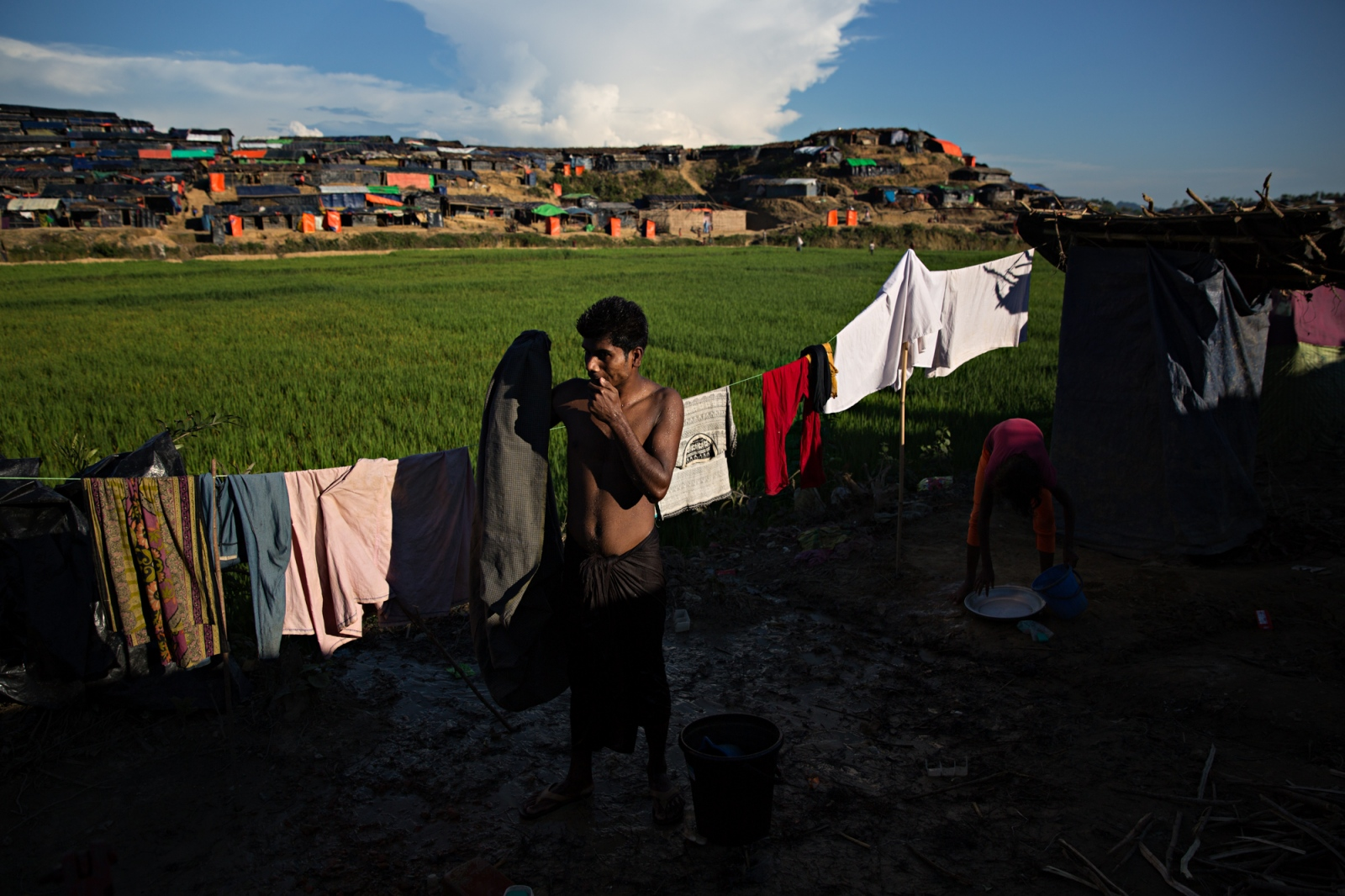 A man washes outdoors at Bagoha camp. The high density of refugees means people have to share every availble resource and space. Showers and bathrooms are drained down the hill sides into the water below.