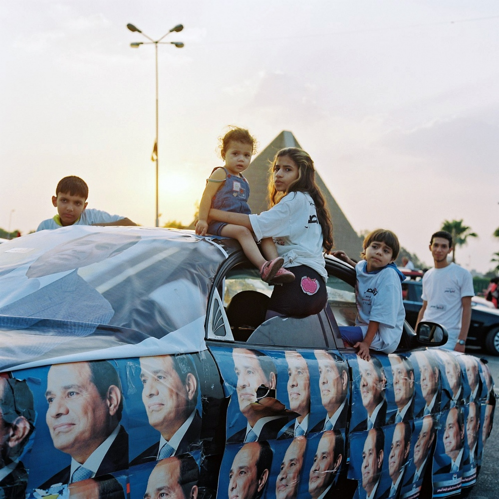 "In Barry Kemp's book ""Ancient Egypt: Anatomy of a Civilization,"" he wrote: ""Akhenaten's kingship provides an unintended caricature of all modern leaders who engage in the trappings of charismatic display."" Here on the eve of Sisi's election day his supporters at pro-Sisi rally arrive in a car pasted with his photographs."
