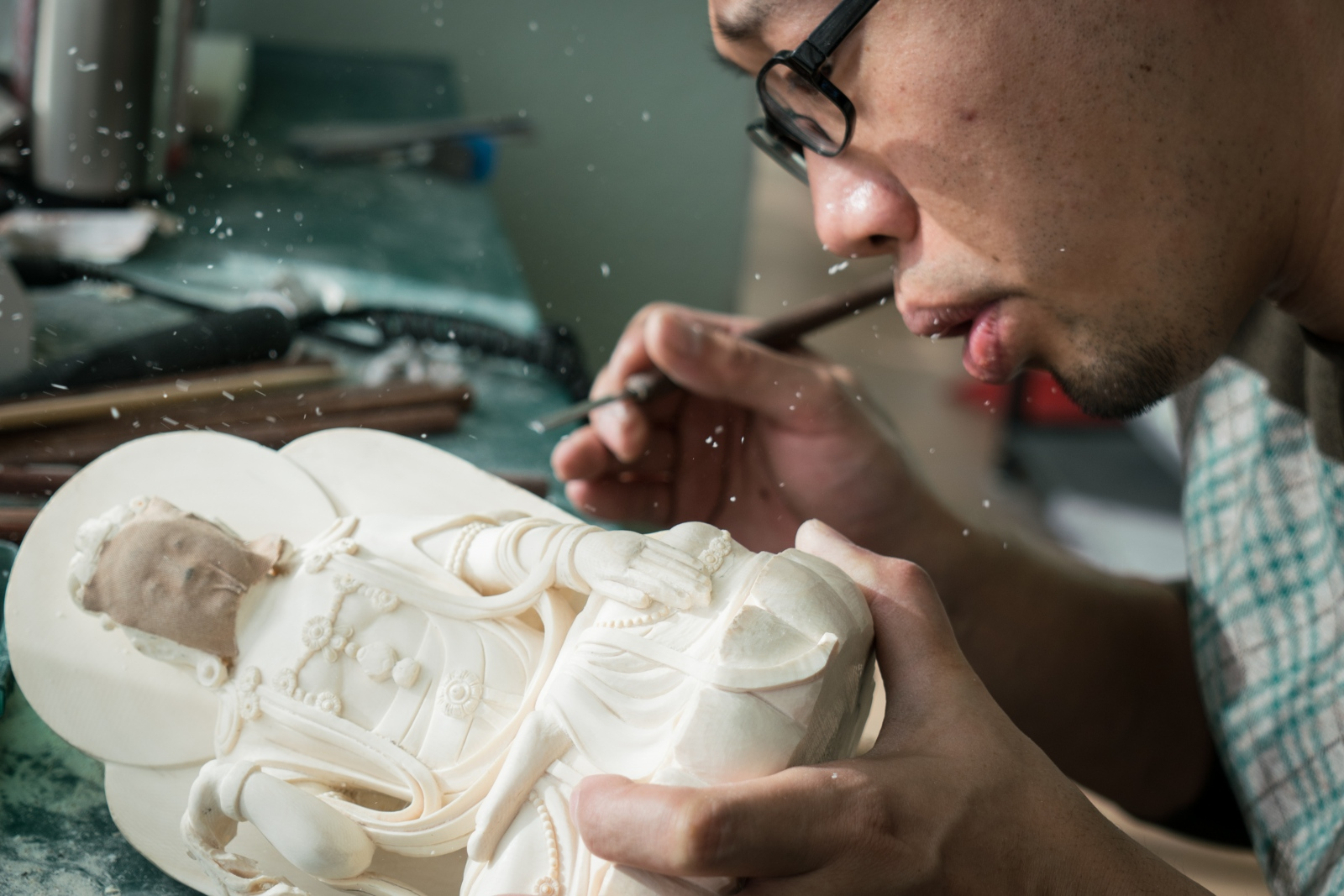 Ivory dust flies as Zhang Yong blows it away during carving at Li Chunke's ivory carving workshop in Beijing, China on December 10, 2017.