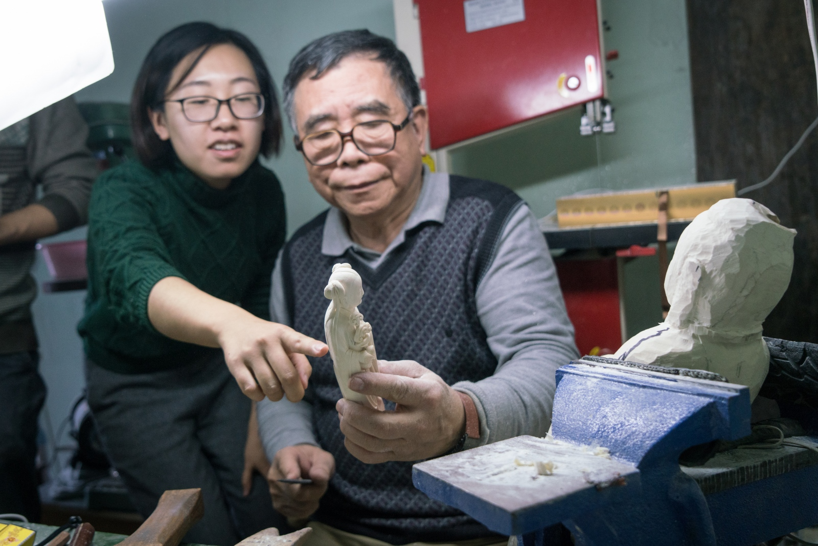 Ivory carving artist Li Chunke comments on the unfinished ivory statue made by Pan Xingjie, a former student who now works at Li's workshop, and offers advice at his ivory workshop in Beijing, China on December 10, 2017.